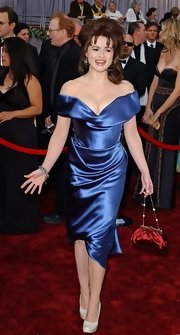 Wacky style icon Helena Bonham Carter wears a surprisingly demure off-the-shoulder gown to the 2006 Oscars. She paired the blue satin frock with a red purse and white pumps.