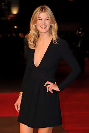 Rosamund wears a little black wrap dress with sleeves and a low plunging neck.  She manages to make this sexy look quite sweet, as well.