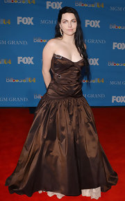 Amy dons an iridescent brown ball gown with a low waist and wrapped buckles around the bodice.