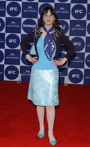 Zooey Deschanel channeled a '60s flight attendant with a royal blue print scarf tied around her neck.