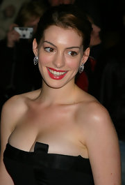 Anne Hathaway brightens up her black ensemble with bright red lipstick.