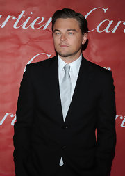 Leo wears a silver tie with a striped sheen.