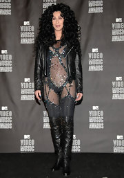 Cher wears a black sheer and sparkly bodysuit. Typical Cher fashion!