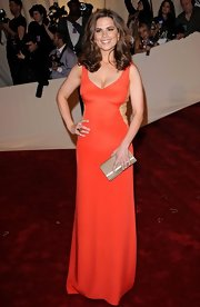 Hayley Atwell accented her stunning orange gown with a metallic champagne clutch.