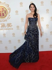 Lucy Liu wowed at the Huading Film Awards in a navy Carolina Herrera strapless gown featuring geometric silver accents.