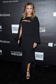 Rita Wilson went for modern elegance at the amfAR Inspiration LA Gala in a black Tom Ford gown with cape-like detailing and an asymmetrical fluted hem.