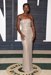 Lupita Nyong'o looked simply flawless in a micro-beaded gold strapless gown by Calvin Klein at the Vanity Fair Oscar party.