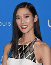 Tao Okamoto punched up her beauty look with bold red lipstick.