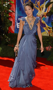 Her V necked dress is complimented with layered necklaces.