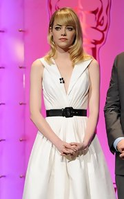 Emma Stone cinched her Andrew Gn dress with a black leather belt.