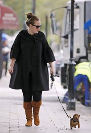 Adele wore a pair of cognac knee-high suede boots while out walking her dog.
