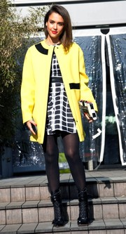 Jessica Alba teamed killer black boots with a bright yellow coat for the Kenzo fashion show.