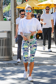 Model Alessandra Ambrosio looks sporty and fit in her activewear. The multi-colored printed yoga pants add a flare of color to her white ensemble.