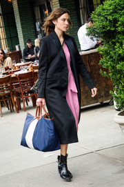 Alexa Chung layered a classic black coat over a pink dress for a day out.