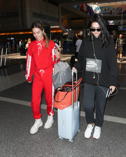 Amelia Hamlin hid her figure under a baggy black hoodie for a flight.