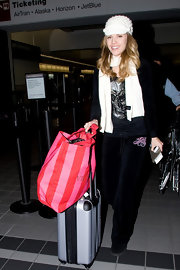 AnnaLynne brightened up her travel gear with a red and pink striped canvas Victoria's Secret tote.
