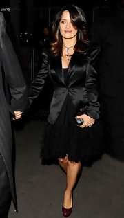 Salma Hayek kept her look dark layering a black silk blazer over a matching dress.