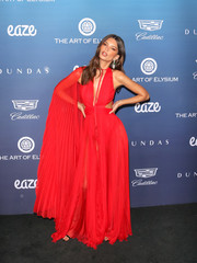 Emily Ratajkowski was hard to miss in this caped red cutout gown by Dundas at the Art of Elysium celebration.