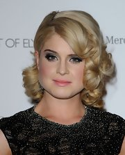 Kelly Osbourne continues her ride on the glamorous train with side swept curls.