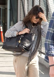 Mila Kunis topped off her ensemble with an oversized black leather tote by Alexander McQueen.