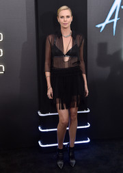 Charlize Theron completed her sultry outfit with a fringed black mini skirt, also by Dior.