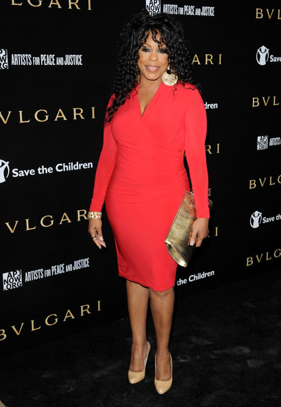 Niecy wears classic nude pumps with her vibrant cocktail dress at the Bvlgari party.