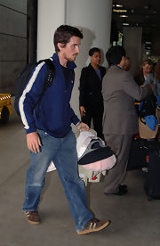 Christian Bale wore a blue striped track jacket while traveling through the airport with his child.