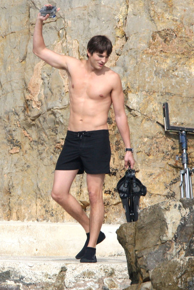 Ashton is ready to dive in these black swim trunks.