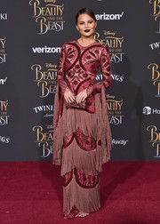 Chrissy Teigen was impossible to miss in this fringed burgundy gown by Raisa & Vanessa at the premiere of 'Beauty and the Beast.'