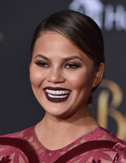 Chrissy Teigen swiped on some dark plum lipstick to match her dress.