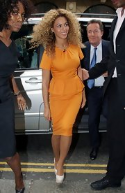 Beyonce teamed her ladylike orange peplum dress with a pair of statuesque white platform pumps.