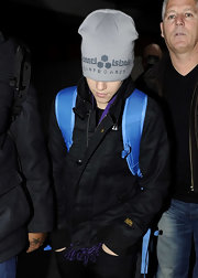 Justin wears a skater beanie with a black jacket and blue backpack at Heathrow airport in London.