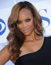 Tyra brought out her hazel eyes with a dark shadow on her low lids.