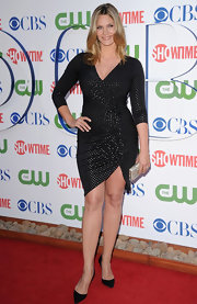 Natasha Henstridge stepped onto the red carpet of the TCA Party in Beverly Hills wearing a silver studded black jersey cocktail dress. The kept the look sophisticated with black pointy-toed pumps.