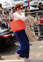 Bryce added a pop of color to her look with a coral tote bag with cutout detailing.