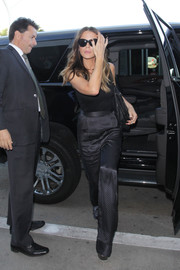 Kate Beckinsale caught a flight out of LAX wearing a sexy black bodysuit by Wolford.