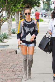 Cara Santana stepped out wearing a patchwork sweater and a pair of ripped denim shorts.
