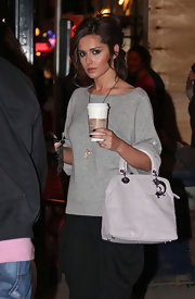 Cheryl's white leather tote bag is from the Lady Dior collection. It features dangling silver logo letters and a criss-cross top-stitched design. This is a very classic and feminine tote.