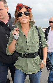 Cheryl Cole showed off her street style while leaving Heathrow airport. She cinched her casual cool look with a double black belt.