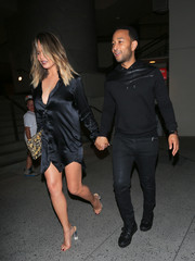 Chrissy Teigen turned heads in a plunging black satin shirtdress by Ann Demeulemeester while enjoying a night out.