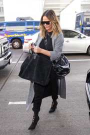 Chrissy Teigen bundled up in a gray Alice + Olivia duster for a flight out of LAX.
