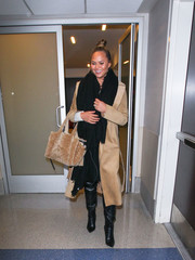 Chrissy Teigen was spotted at LAX looking edgy-glam in a beige suede coat.