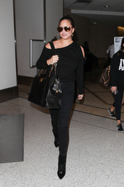 Chrissy Teigen was modern and edgy in a black cold-shoulder sweatshirt by RtA while catching a flight.