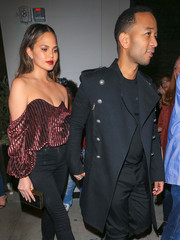 Chrissy Teigen teamed a black and gold Monique Lhuillier box clutch with an off-the-shoulder top and jeans for a date night at Catch.