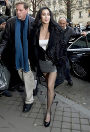 Cher arrived at the 'Burlesque' photocall looking glam in a black fur coat layered over a mini dress.