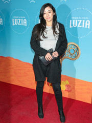 Aimee Garcia accessorized with a black leather clutch.