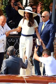 Radiant bride Amal Alamuddin took a boat ride in Venice wearing a loose white blouse with blue trim designed by Stella McCartney.