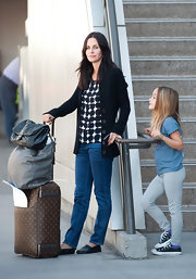 Coco Arquette waited patiently at LAX for her pick-up in a pair of black canvas Chucks.