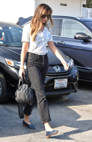 Dakota Johnson headed out in LA wearing a white polo shirt with blue pinstripes.