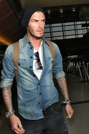 David Beckham travels through the airport in a soft denim button down shirt.